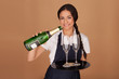 Beautiful waitress pouring champagne