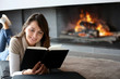 canvas print picture - Portrait of beautiful woman reading book by fireplace