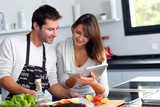 Fototapety Couple in home kitchen using electronic tablet