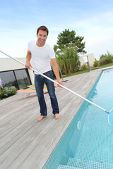 Man cleaning swimming-pool in private villa