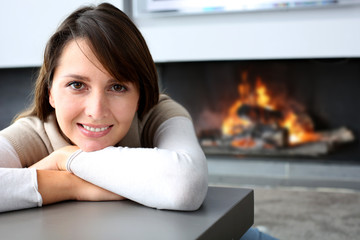 Beautiful woman sitting by fireplace at home