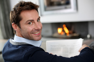 Man at home reading newspaper in front of fireplace