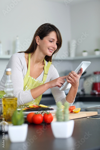 Woman in kitchen looking for dish recipe on internet