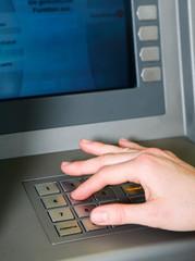 Frau holt Geld am Geldautomat