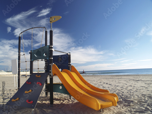 Playground slide and children's area in a beach.