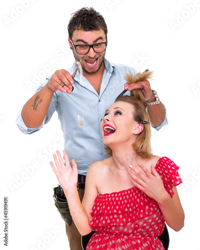 Hairdresser cutting woman's hair, studio shot