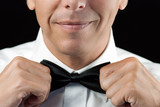 Man In Tux Straightens Bowtie, Two Hands poster