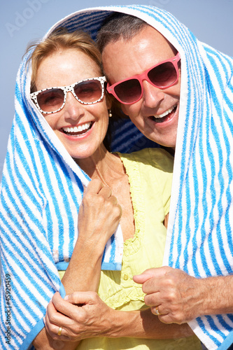 Senior Couple Sheltering From Sun On Beach Holiday