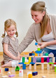 Child and woman having fun playing with building blocks