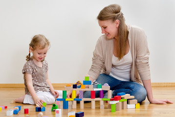 Cute little girl and young woman playing in blocks