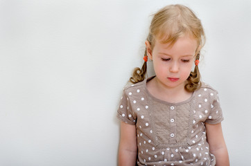 Portrait of sad little girl standing against the wall.