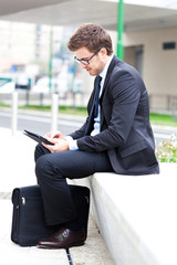 Businessman using a tablet sitting outdoor