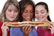 Three female friends sharing long sandwich