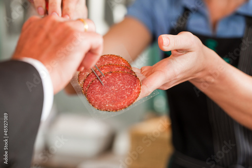 Butcher Showing Fresh Meat Steaks to Customer