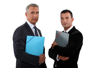 Two businessmen standing and holding files.