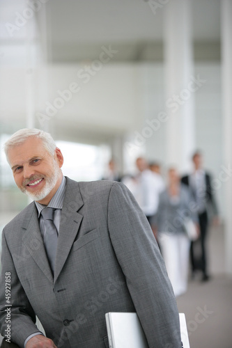 senior businessman holding a laptop