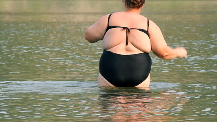 woman with overweight bath in river