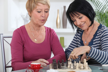 Two female friends playing chess