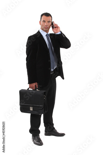 Serious businessmen with a cellphone