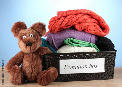 Donation box with clothing on blue background close-up