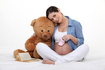 A pregnant woman with a teddy bear.