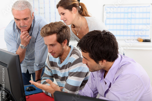 Group of people sitting round a computer