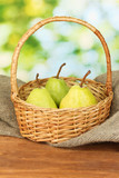 Ripe pears on colorful green background