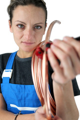 Female plumber with copper pipe
