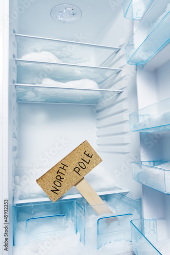 Fridge with frost and North Pole sign. Global warming