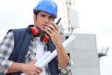 Tradesman speaking into a walkie talkie poster