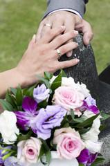 Руки молодоженов с обручальными кольцами на камне
