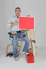 Carpenter holding a blank red sign