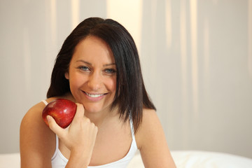 Woman with a red apple in bed