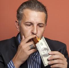Man lighting his cigar with 100 dollars banknote