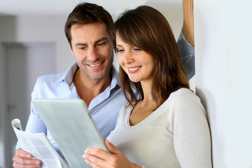 Couple at home reading news on newspaper and internet