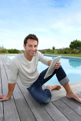Man sitting by pool with digital tablet