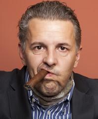 Man wearing suit gangster style smoking cigar