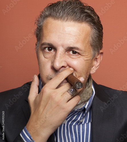 Man wearing suit gangster style smoking cigar