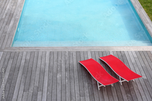 View of red long chairs set by swimming-pool