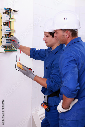 Two electricians performing checks