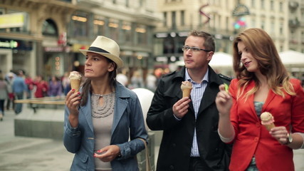 Happy friends eating ice cream in the city, steadicam shot