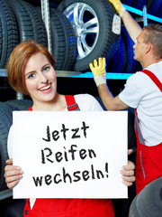 Female car mechanic is showing blackboard with tire changing