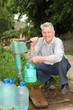 Grandfather takes water to plastic bottle from hydrant