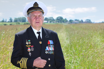 Grandfather in form, cap, ordens, medals pose in field