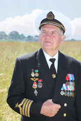 Grandfather in form, cap, ordens, medals hold hand form in field