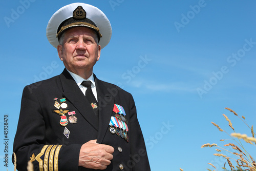 Grandfather in form, cap, ordens, medals pose background sky