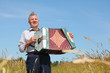 Grandfather in shirt play on accordion, sing in field
