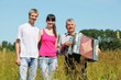 couple stand near grandfather with accordion in field