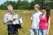 Grandfather play on accordion with couple in field