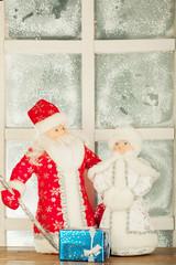 miniature toy Santa Claus, Snow Maiden near frost window